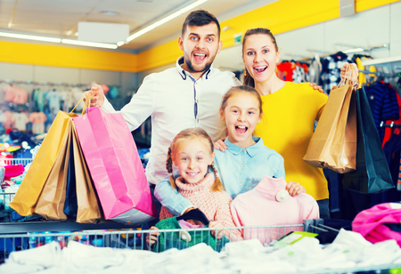 smiling friendly young family of four with shopping bags in clothing shop