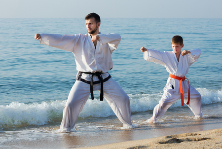 Happy young man and boy exercising karate in morning outdoor