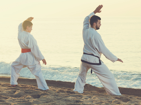 Man and boy in uniform practising karate poses at sunny sea beach