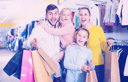 glad family of four with shopping bags in clothing shop