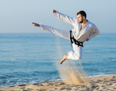 Man demonstrates kung-fu poses at seaside in sunset outdoor Stock Photo