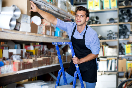 Adult man in unifom is standing on ladder near shelves in the building store Foto de archivo