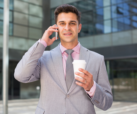 Business man talking on mobile phone outdoors with disposable cup in hand Stock Photo