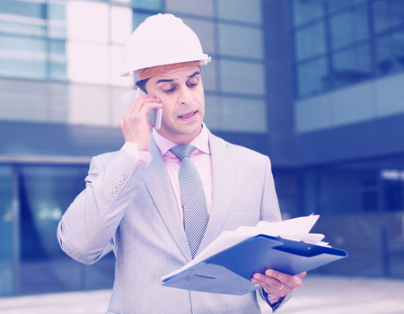 Businessman holding papers and having phone call conversation outdoor
