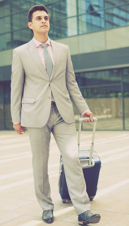 Young successful businessman carrying suitcase while going to business trip
