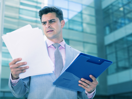 Businessman holding folder with documents and attentively reading Stock Photo
