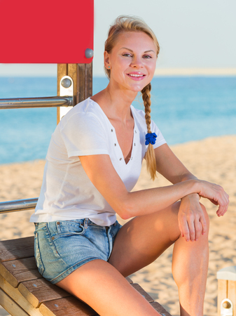 Active woman in white T-shirt is resting after training on the beach