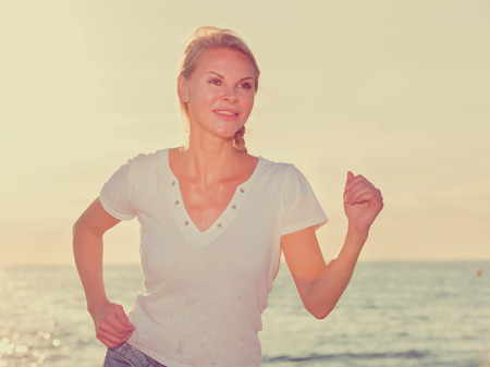 Sportswoman is jogging on the beach near the ocean.