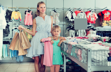 Pretty mother with daughter holding packages with purchases in the dress shop