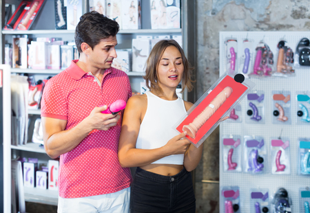 adult spanish woman and man bayers choosing long rubber phallus in the sex shop
