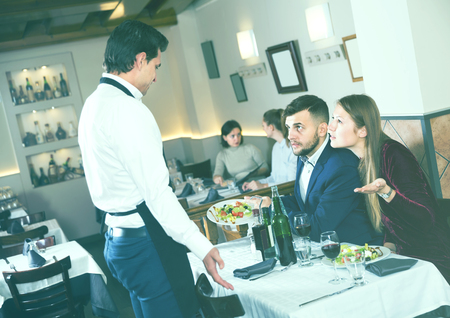 angry guests conflicting with waiter because of poor quality of dish in restaurant Stock Photo