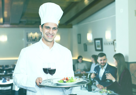 Handsome male chef with serving tray welcoming to restaurant