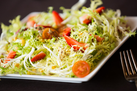 Closeup view on a green salad with cherry tomatoes and strawberries, served and ready to eat Stock Photo
