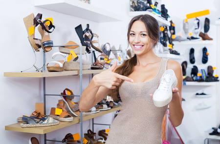 Happy brunette woman holding desired shoe in hands in fashion boutique