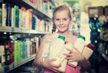 Positives Mädchen , das Shampoo und Duschgel im Supermarkt hält Standard-Bild - 95004237
