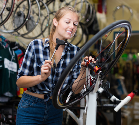 Young woman master repairing wheel of sportbike in bicycle store