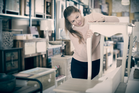 happy buyer standing near nightstand in furniture shopping room