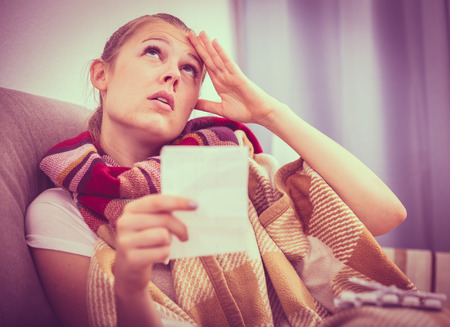 Sad young female lying at sofa reading recipe with pills