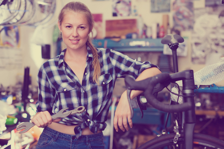 Portrait of happy girl who is fixing her bicycle indoors