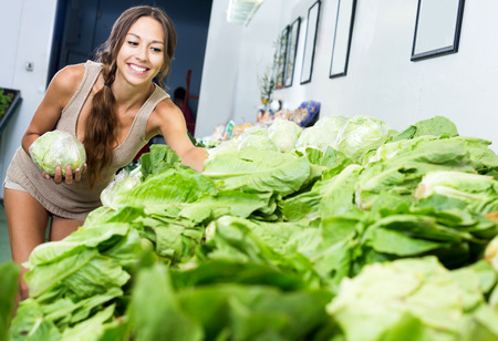 Portrait of young happy woman shopping fresh green lettuce in shop