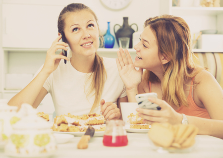 Girlfriends are playfull talking by phone at home.