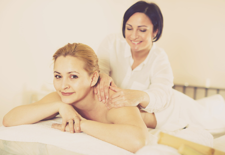 Adult woman on massage procedure in Spa salon where bamboo sticks are used