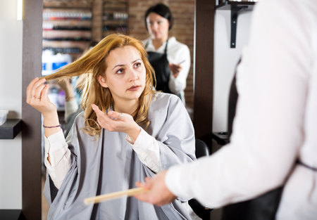 Girl telling to hairdresser that she does not like her hairstyle
