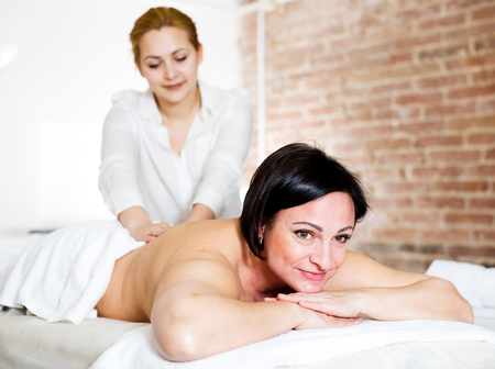 Happy adult woman very happy with procedure of massage in beauty parlor