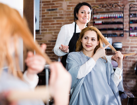 Young  positive woman points to master in hairdress salon right hair length for haircut