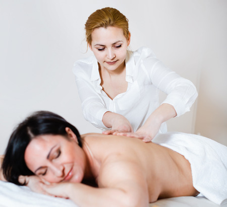 Young  cheerful positive massagist doing shoulder massage to adult woman in spa salon