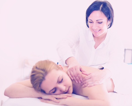 Aged massagist is doing relaxing massage shoulder area for young woman in spa salon.  Imagens
