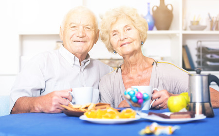 Portrait of happy mature couple having good time drinking tea in kitchen