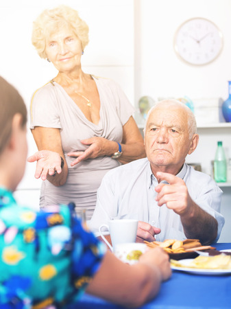 Stressed senior couple having conversation with female over cup of coffee at home Stock Photo