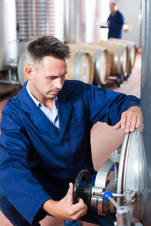 portrait of man working on secondary fermentation equipment in winery manufactory