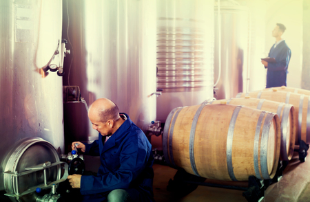 Glad man machinery operator working on secondary fermentation equipment in winery manufactory
