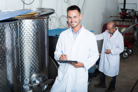 Smiling young man standing with cardboard in secondary fermenting section on winery