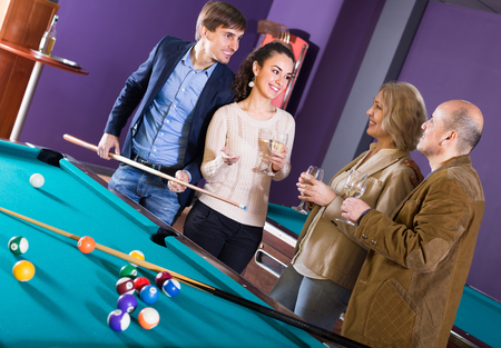 Group of cheerful smiling different age friends with wine chatting near billiard table