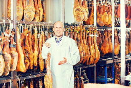 Mature experienced butcher posing with jamon joints at a meat factory