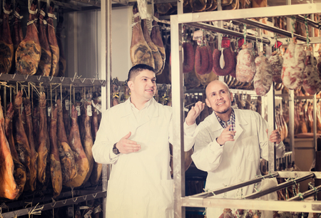 Two technologists  in white gown discussing quality of sausages and jamon
