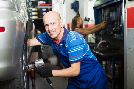 Happy mechanic man working with impact tire fitting tool in service point