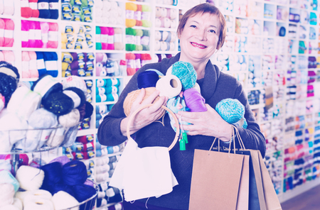 Pleasant  woman holding shopping bags and accessories for knitting and embroidery Stock Photo
