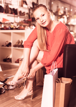 Female buyer is trying on sandals for summer season in boutique. Stock Photo