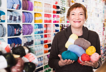 Portrait of smiling mature female during shopping in needlework store
