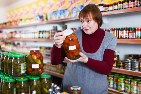 Woman consumer choosing glass jar of tomatoes in the food store  Stock Photo