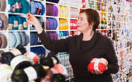 Beauty senior woman choosing yarn for knitting in needlework shop