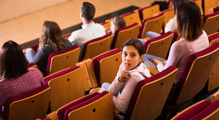 Female teenager looking away from screen in cinema house