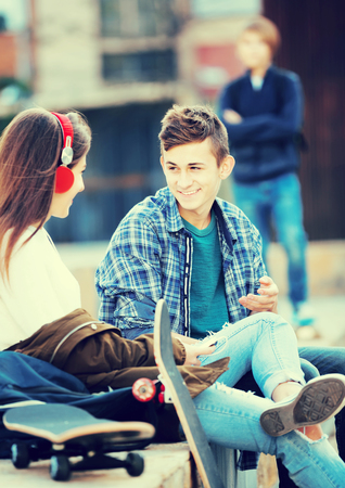 Envy male teen standing aside of girlfriend talking with boy outdoors