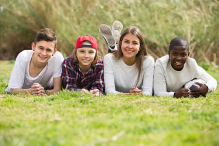 Group of joyful teenage friends having fun outdoors lying on the grass Banque d'images
