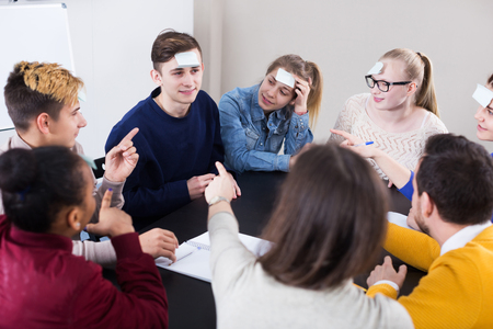 Positive male and female students playing guess-who game in school Stock Photo