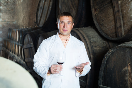 Glad young male in robe keeping ageing process of wine under control Stock Photo